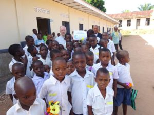 Happy faces in front of the new school building in Kabinda